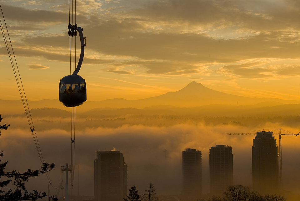 Aerial Tram with fog over the Willamette River with Mt. Hood at sunrise.